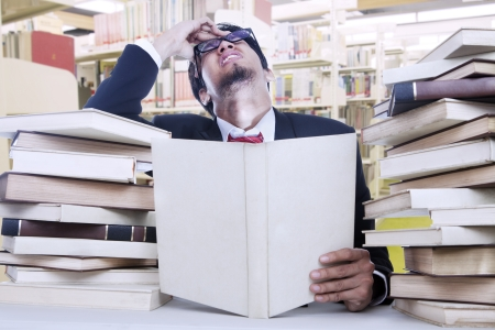 Young businessman is stressful after reading lots of books in the library photo