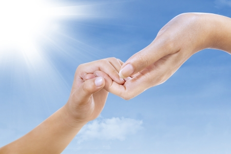 Hand gestures of two hands mother and child holding hands\ under blue sky