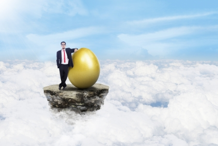 Businessman is standing beside a golden egg above the clouds Stock Photo - 17533494