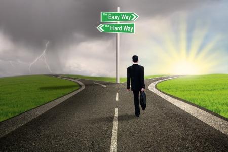 cruce de caminos: Hombre de negocios est� caminando por el carril de la manera f�cil con el fondo tormentoso