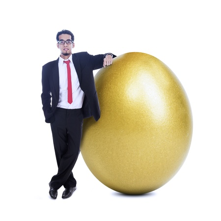 Businessman is standing beside a big golden egg on white background photo