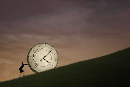Businesswoman is pushing a big time clock on top of a hill  The clock is written Time photo