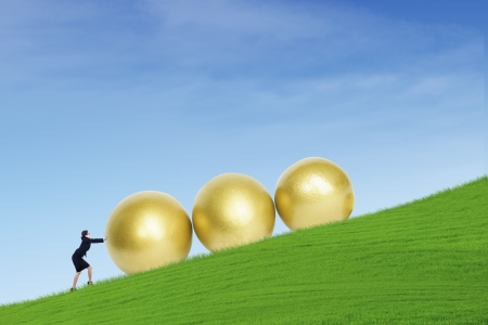 Businesswoman is pushing three golden eggs on top of green hill