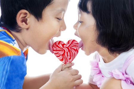 Brother and sister are licking heart shape lollipop on white background photo