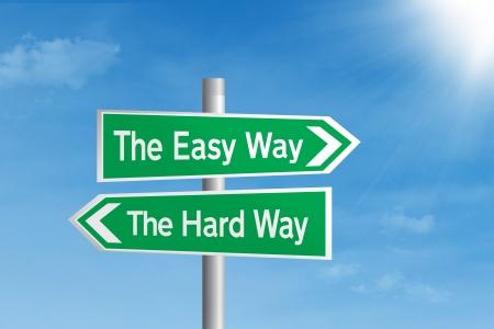 split road: Easy way vs Hard way road sign under blue sky Stock Photo