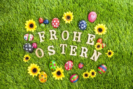 Easter eggs laying on the grass with wooden letter Frohe photo