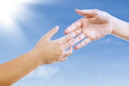 Mother is about to give a handshake to her son under blue sky photo