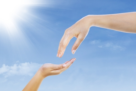 charity work: A mother giving something to her child under blue sky