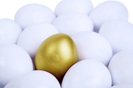 A golden egg in between common eggs isolated on white Stock Photo - 17573368