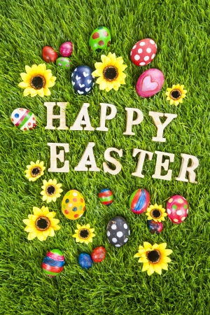 Easter eggs and greeting wooden alphabet on the grass photo