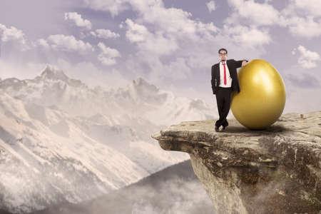 businessman standing: Confident businessman standing on top of a mountain beside golden egg