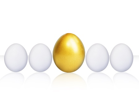 Bigger and unique golden egg in the middle isolated over white background photo