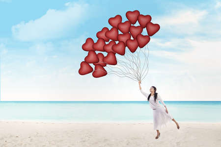 valentine s day beach: Young woman is holding heart shape balloons on the beach