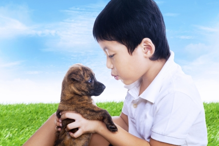 2 5 months: Boy and his puppy outdoors under blue sky