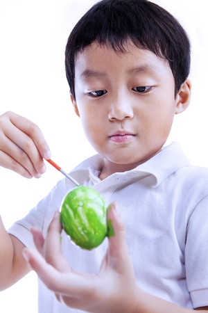 creative egg painting: Serious boy is painting green easter egg isolated on white