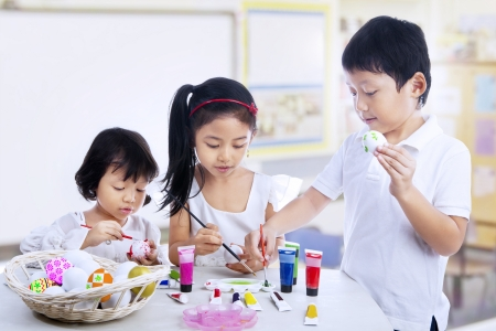Children are painting easter eggs in art class photo