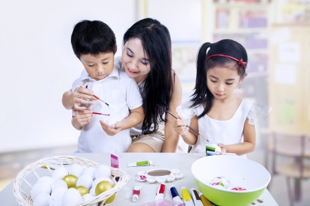 cousin: Happy family painting easter eggs in art class Stock Photo