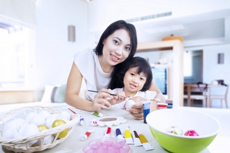 creative egg painting: Mother and daughter are painting easter eggs in class room
