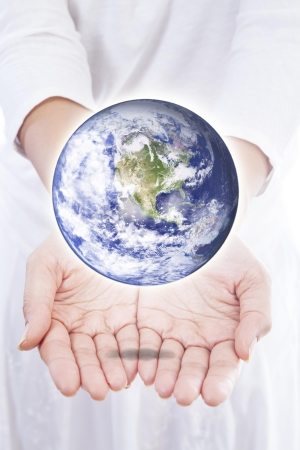 Woman holding planet earth in her hands, isolated on white photo