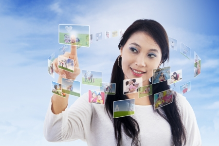 Beautiful woman touching digital photos and contact person on touchscreen Stock Photo - 22632553