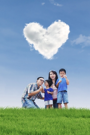 under heart: Family is having fun in the park while blowing bubbles with children under heart shape clouds