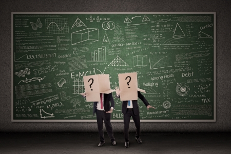 confused man: Two businessmen with question mark boxes standing in front of blackboard
