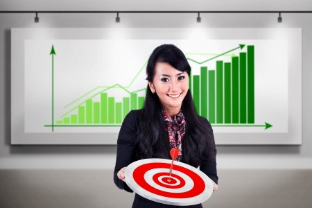 Happy businesswoman holding dartboard while standing in front of profitable bar chart Stock Photo - 17824186