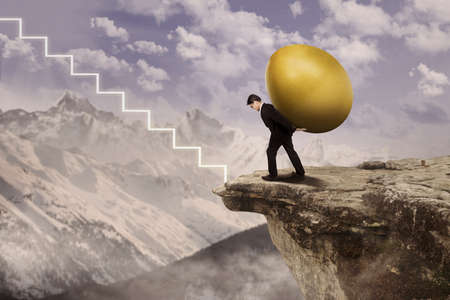 Businessman carry gold egg on top of a mountain towards virtual stairs Stock Photo - 17824199
