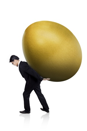 priceless: Businessman is carrying a huge golden egg isolated on white