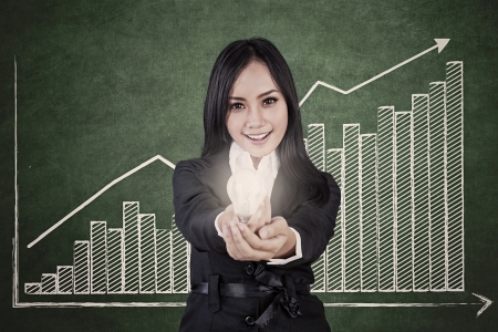 Businesswoman is holding a bright light bulb with profit bar chart showing increase in value photo