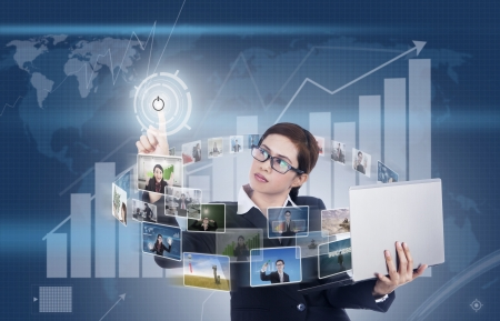 Businesswoman holding a laptop and pressing a touchscreen on profit bar chart background photo