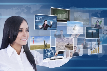 Businesswoman is using digital touchscreen to choose photospictures photo