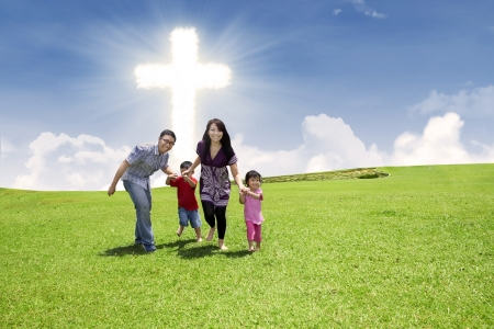 Christian family is running over the green field under bright Cross sky photo