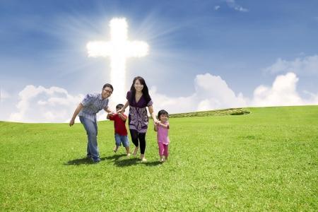 familia cristiana: Familia cristiana est� corriendo sobre el campo verde bajo el cielo brillante de la Cruz Foto de archivo