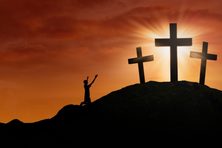 worshipper: Christian worshipper is sitting on the hill beside the cross on sunset background Stock Photo