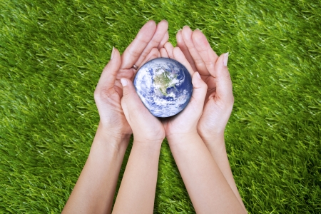 Gesture of two hands (mother and son) on the grass holding planet Earth photo