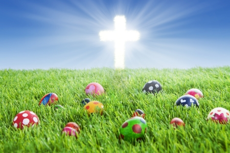 egg laying: Picture of colorful easter eggs laying on the grass with a bright Cross Stock Photo