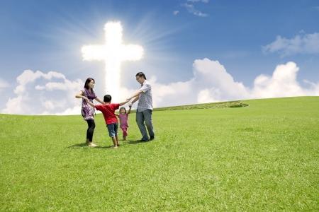 familia cristiana: Familia cristiana disfrutando de sus vacaciones de Pascua en el parque bajo el signo de la Cruz brillante