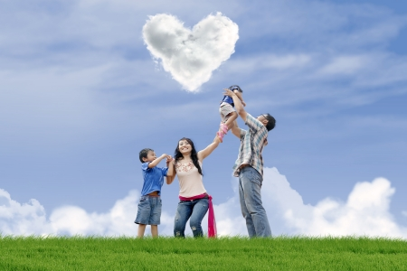 under heart: Young family is having fun under heart shape clouds in the park