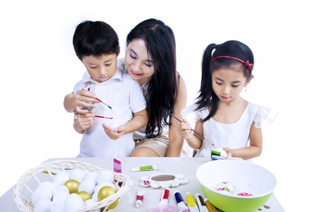 Happy family are painting easter eggs isolated over white background photo
