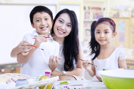 creative egg painting: Mother and children are painting in a classroom