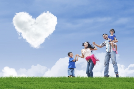 under heart: Family having fun in the park under heart shape clouds