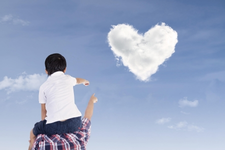 man looking at sky: Father and son are pointing at heart shape clouds under blue sky