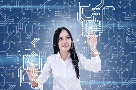 futuristico: Bella donna selezionando touchscreen futuristico su sfondo blu