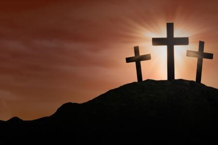 cruz religiosa: silueta de tres Cruces firme en la cima de una colina Foto de archivo