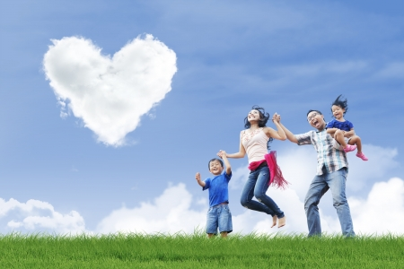 Happy family is having fun under love shape clouds in the park photo