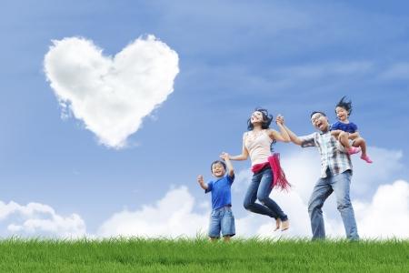 familias felices: La familia feliz se divierten bajo las nubes forma de amor en el parque