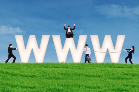 Business people using communication tools surround www letter on the green field photo