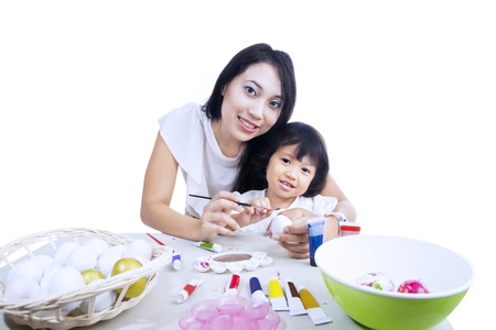 Mother and daughter painting easter eggs, isolated on white photo