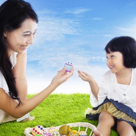 indonesian woman: La madre est� dando un huevo de Pascua a su hija al aire libre, bajo el cielo azul Foto de archivo